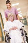 A Nurse Pushing A Senior Woman In A Wheelchair Down A Hospital C — Stock Photo