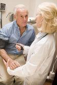 Doctor Measuring Mans Blood Pressure — Stock Photo