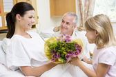 Young Girl Giving Flowers To Her Mother In Hospital — Stock Photo