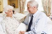 Uomo anziano seduto con la moglie in ospedale — Foto Stock