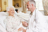 Doctor Laughing With Senior Woman In Hospital — Stock fotografie