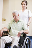 Nurse Pushing Man In Wheelchair — Foto Stock