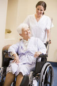 Nurse Pushing Woman In Wheelchair — Stock Photo