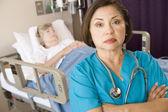 Arts permanent met gekruiste in patiënten kamer armen — Stockfoto