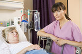 Nurse Checking Up On Patient Lying In Hospital Bed — Stock Photo