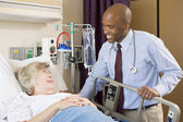 Doctor Talking To Senior Woman Lying In Hospital Bed — Stock Photo