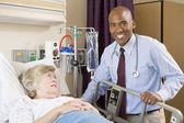 Doctor Checking Up On Patient Lying In Hospital Bed — Stock Photo