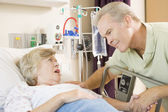Middle Aged Man Talking To Senior Woman In Hospital — Stock Photo