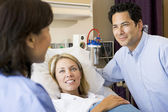 Doctor Talking To Pregnant Woman And Her Husband — Stock Photo
