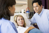 Doctor Talking To Pregnant Woman And Her Husband — Stockfoto
