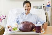 Женщина, сидящая в больничной койке с подносом пищи — Стоковое фото