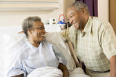 Senior Couple Smiling At Each Other In Hospital — Stock Photo