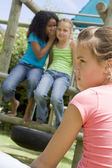 Two young girl friends at a playground whispering about other gi — Stock Photo