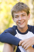 Young boy sitting outdoors smiling — Stock Photo