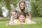 Three young girl friends piled on each other outdoors smiling — Stock Photo