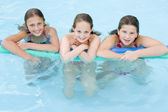 Three young girl friends in swimming pool with pool noodle smili — Stock Photo