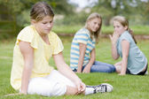 Two young girls bullying other young girl outdoors — Stockfoto
