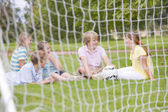 Five young friends on soccer field talking and smiling — Stock Photo
