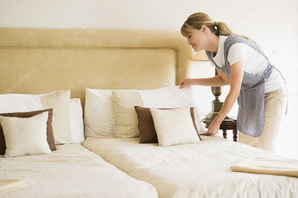 Maid Making Bed In Hotel Room Smiling Stock Photo