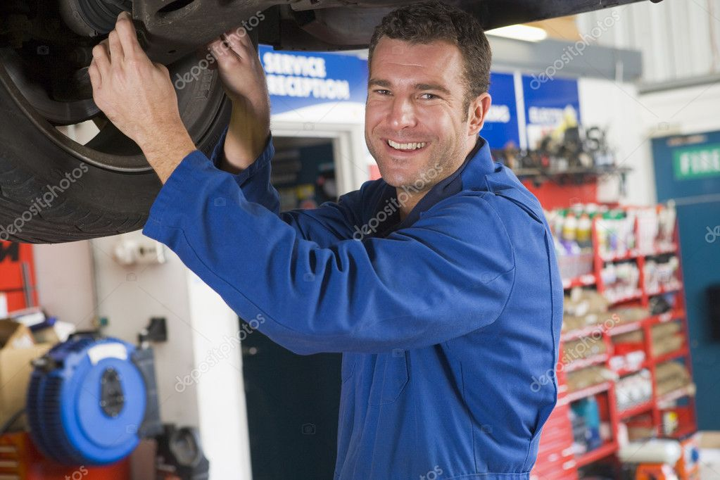 Mechanic working under car smiling — Stock Photo #4770499