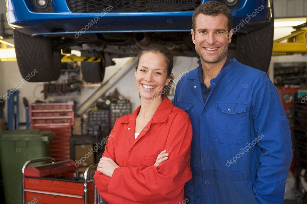 Two mechanics standing in garage smiling — Stock Photo #4770526
