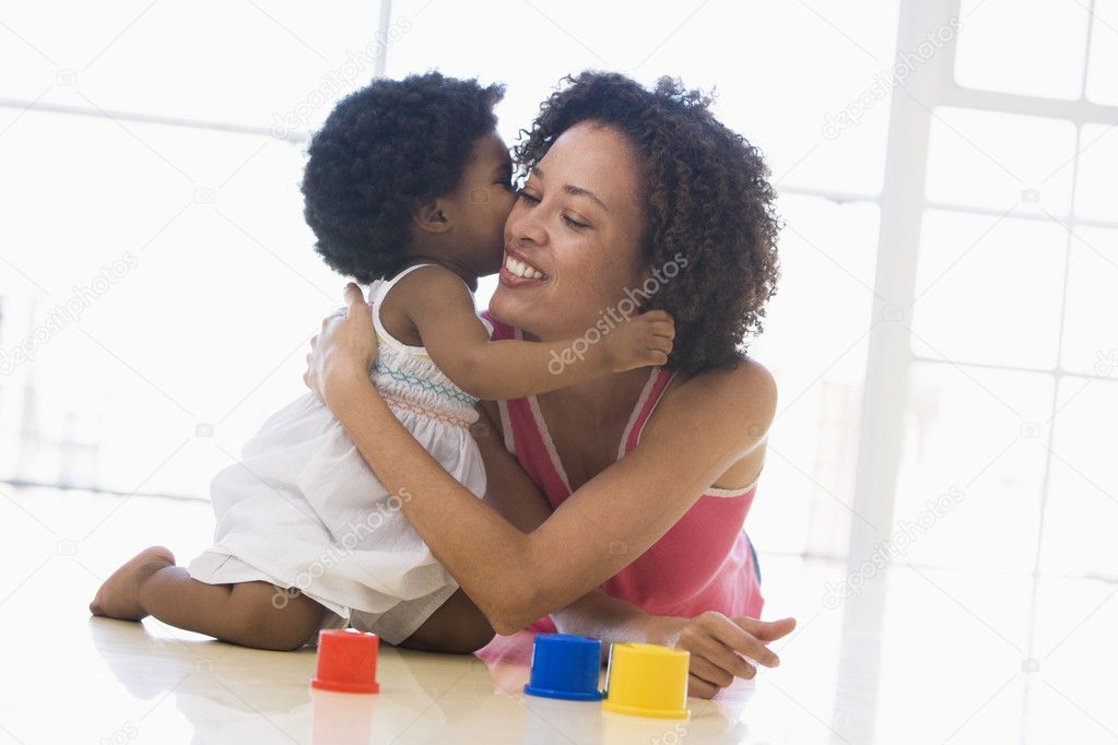 Mother and daughter indoors kissing and smiling — Stock Photo #4770719