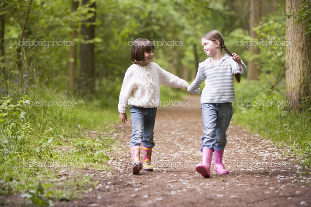 Two sisters walking on path holding hands smiling - Stock ImageTwo Sisters Holding Hands