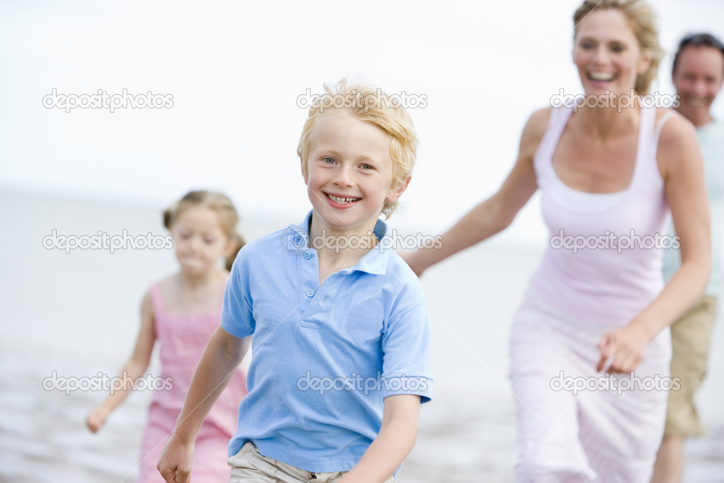 Family running on beach smiling  Stock Photo #4771145