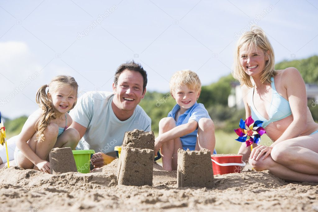 Family on beach making sand castles smiling — Stok fotoğraf #4771175