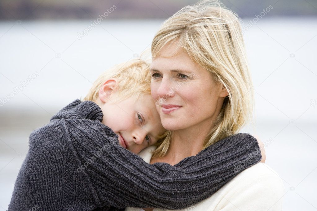 Mother holding son at beach smiling  Stock Photo #4771456
