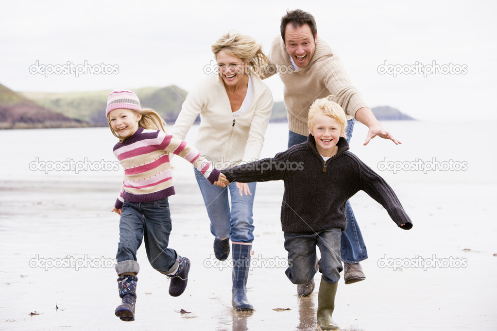 Family running on beach holding hands smiling — Stock Photo #4771564