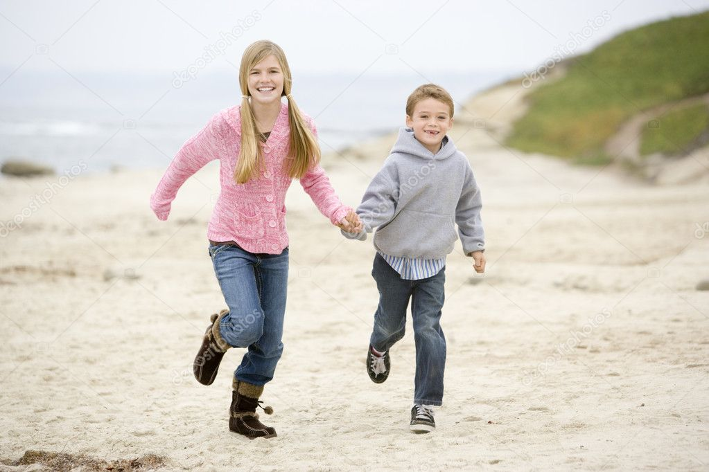 Two young children running on beach holding hands smiling — Stock Photo #4771606