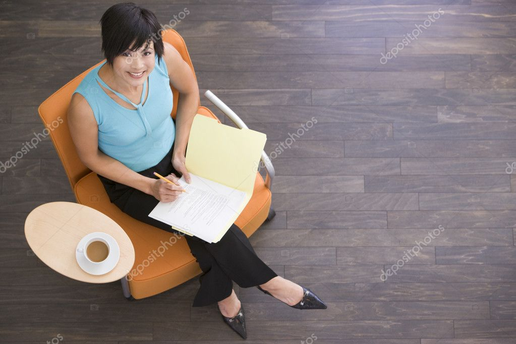 Businesswoman sitting indoors with coffee and folder smiling  Stock Photo #4771946