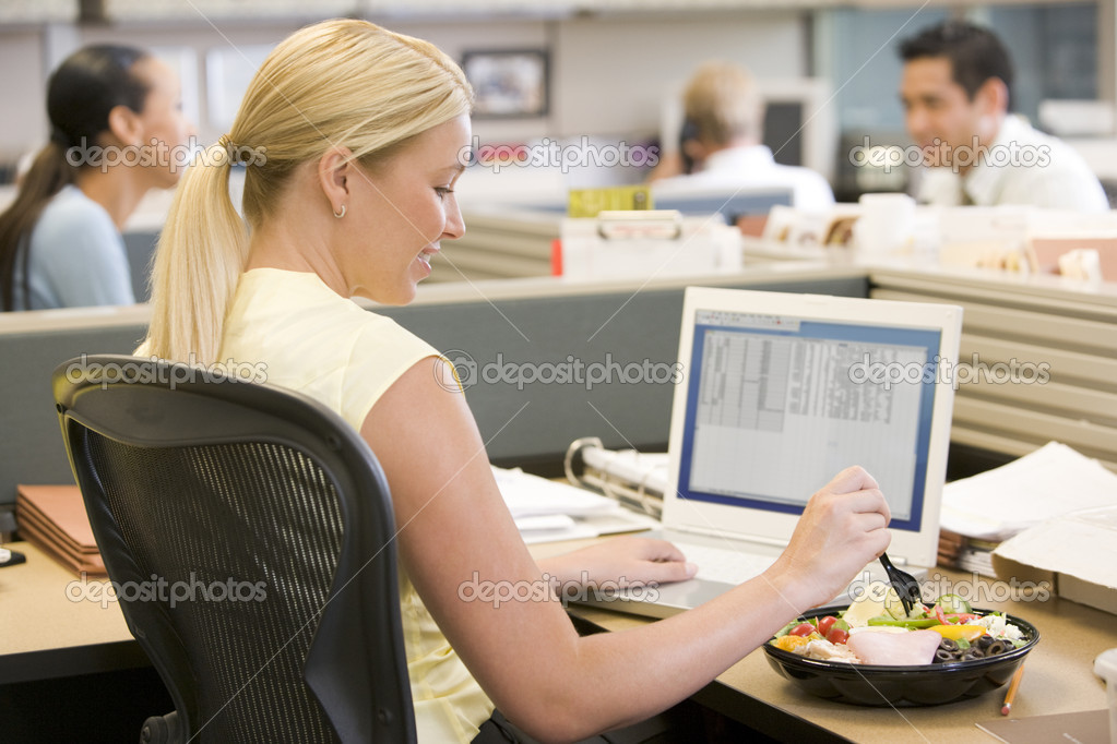 Businesswoman in cubicle using laptop and eating salad — Stock Photo #4772013