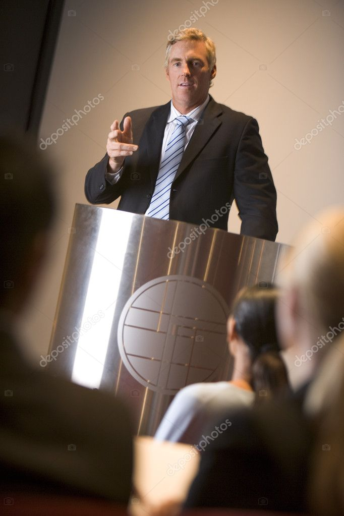 Businessman giving presentation at podium — Stock Photo #4772066