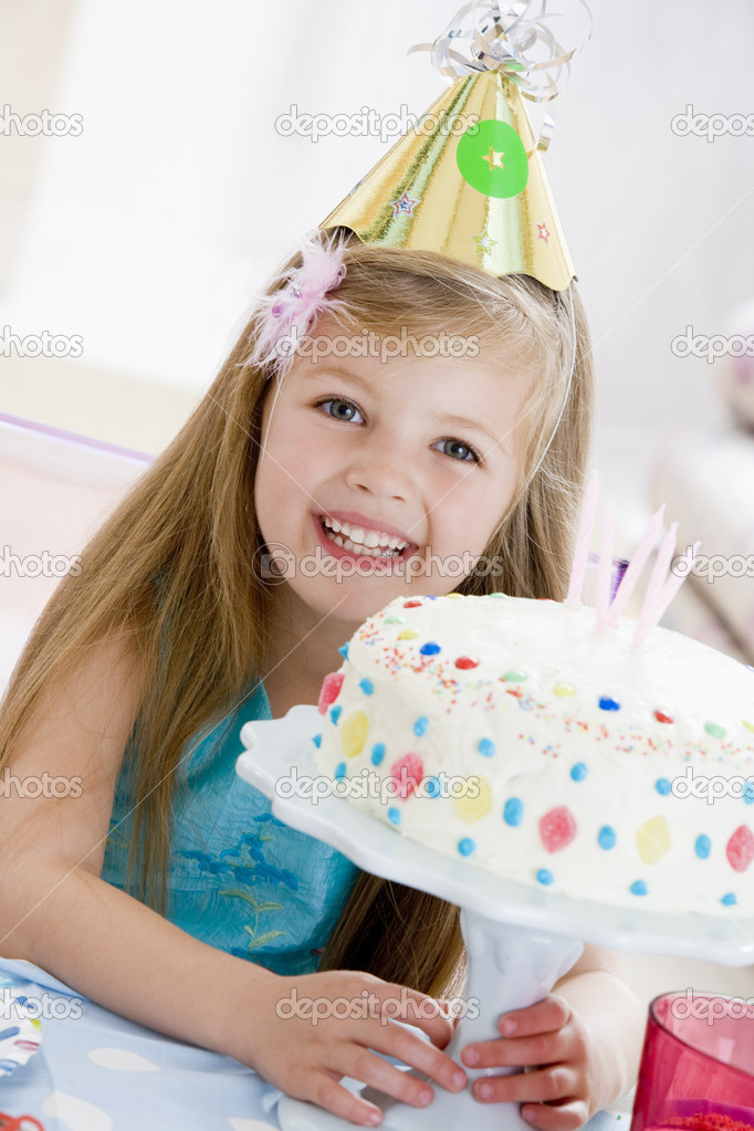 Young girl wearing party hat with birthday cake smiling — Stok fotoğraf #4778274