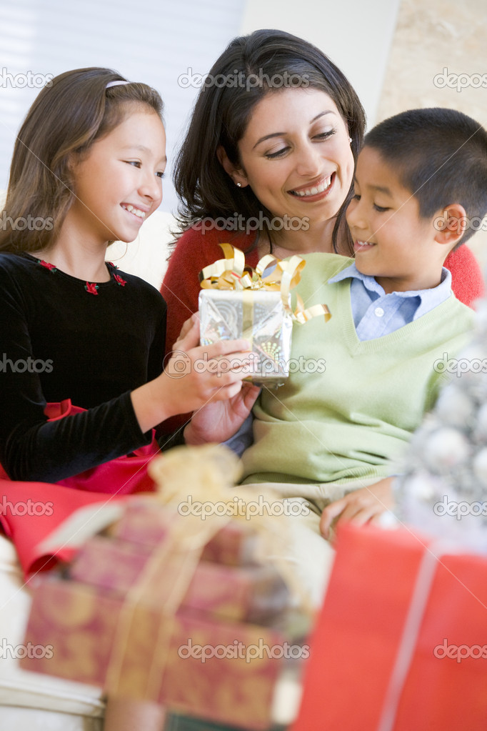 Mother Sitting With Her Son And Daughter,Exchanging Christmas Gi — Lizenzfreies Foto #4778313
