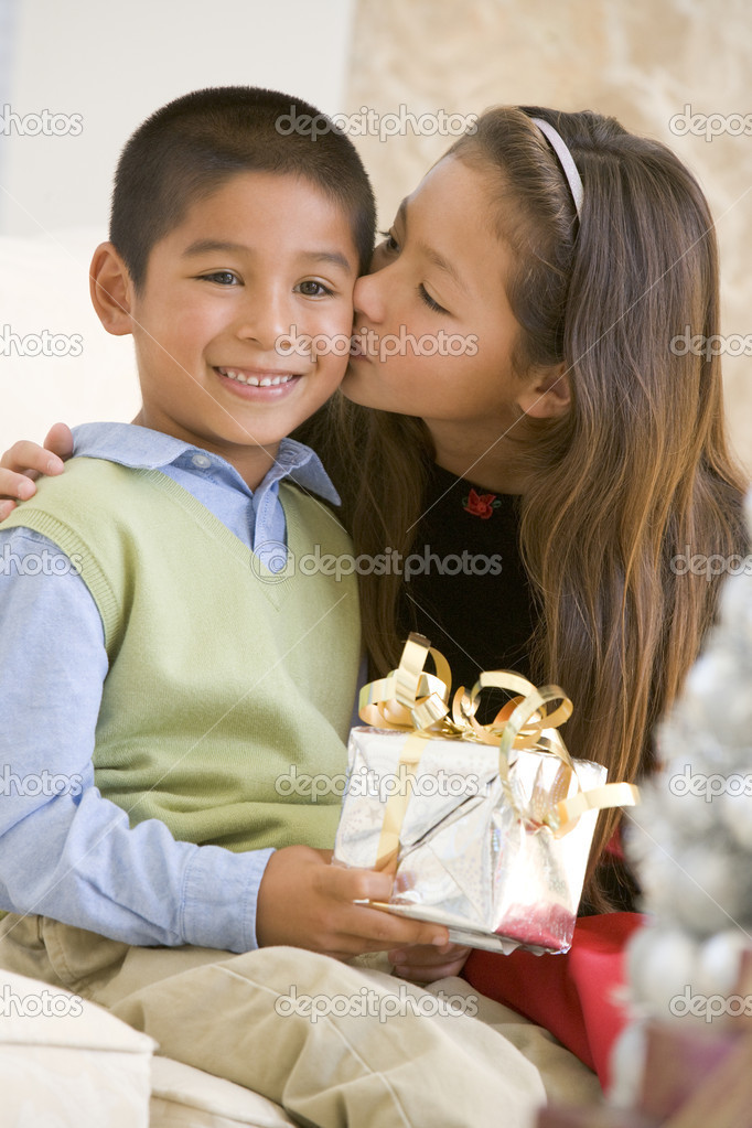Sister Giving Her Brother A Christmas Present And Kissing Him On — Lizenzfreies Foto #4778345