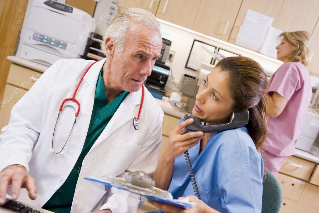 A Doctor And Nurse At The Reception Area Of A Hospital — Stock Photo #4779200