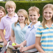 Five young friends with rackets on tennis court smiling — Stock Photo #4780003