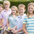 Five young friends with rackets on tennis court smiling — Stock Photo
