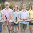 Five young friends with rackets on tennis court smiling — Stock Photo #4780005