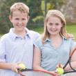 Royalty-Free Stock Photo: Two young friends with rackets on tennis court smiling