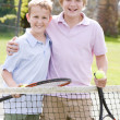 Two young male friends with rackets on tennis court smiling — Stock Photo