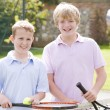 Stock Photo: Two young male friends with rackets on tennis court smiling