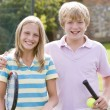 Young couple with rackets on tennis court smiling — Stock Photo