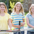 Stock Photo: Three young girl friends with rackets on tennis court smiling