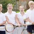 Four young friends with rackets on tennis court smiling — Stock Photo