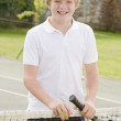 Young boy with racket on tennis court smiling — Stock Photo
