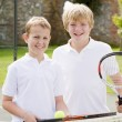 Two young male friends with rackets on tennis court smiling — Stock Photo #4780032